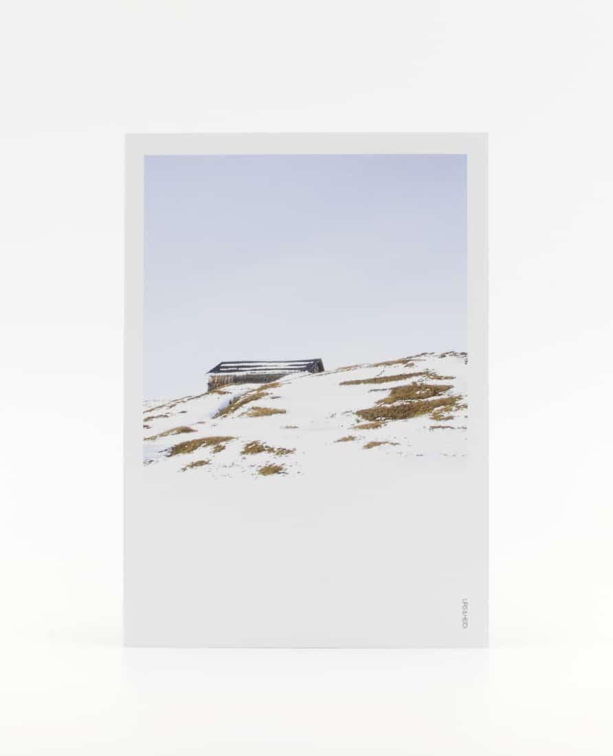 Postkarte im Polaroid Stil mit Alphütte auf Berghügel und blauem Himmel