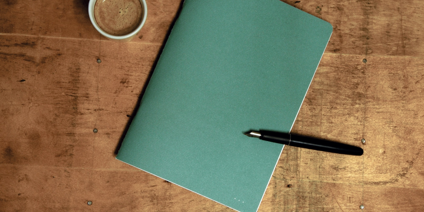 Notizheft grün auf Holz mit Kaffee